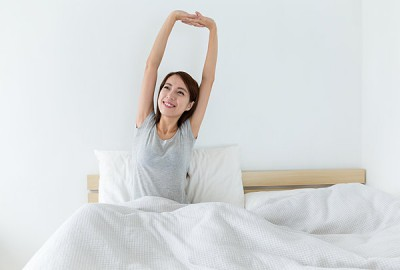 Young woman waking up happily, after a good night sleep